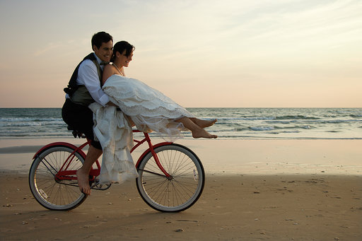 Couple Riding Bike on Beach